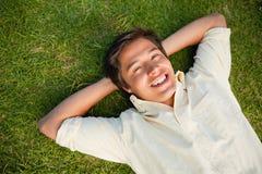 Bemannen Sie das Lächeln, wie er mit beiden Händen hinter seinem Stutzen liegt Stockbild