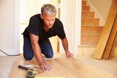 Bemannen Sie das Legen des Täfelungsbodenbelags während einer Hauserneuerung lizenzfreies stockfoto