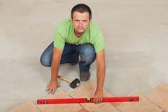 Bemannen Sie das Legen von keramischen Bodenfliesen - überprüfend mit einer waagerecht ausgerichteten, Draufsicht Stockfoto