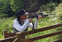 Bemannen Sie das Lehnen auf einem hölzernen Gatter mit einer Gewehr Stockfotos