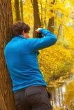 Bemannen Sie das Lehnen gegen einen Baum und das Nehmen Foto von von herbstlichen Vorderteilen Lizenzfreie Stockfotografie