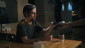 Bemannen Sie das Leisten von Zahlung durch NFC-Technologie am Handy im Café, Studentenlohn-Kaffeerestaurant stock video footage
