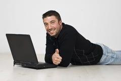 Bemannen Sie das Lügen auf Fußboden mit Laptop und geben Sie Daumen Lizenzfreie Stockbilder