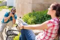 Bemannen Sie das Machen der Fotos der Frau auf Bank Stockbilder