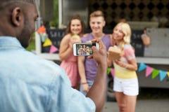 Bemannen Sie das Machen des Fotos der Freunde, die am Lebensmittel-LKW essen Lizenzfreie Stockfotografie