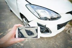 Bemannen Sie das Machen des Fotos des schädigenden weißen Autos mit Smartphone Lizenzfreie Stockbilder