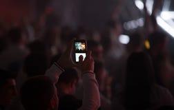 Bemannen Sie das Machen des Fotos eines Konzerts mit Smartphone Lizenzfreies Stockbild