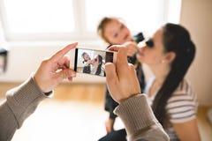 Bemannen Sie das Machen des Fotos mit Smartphone seiner Frau und ihres daughte Stockbild