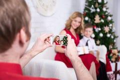 Bemannen Sie das Machen des Fotos seiner Frau und Sohns mit Weihnachtsbaum Stockbilder