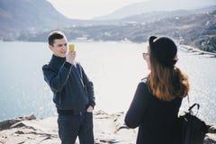 Bemannen Sie das Machen des Fotos seiner Freundin, die seinen Smartphone nahe Küste und Bergen verwendet stockbilder