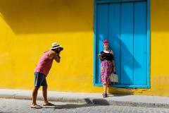 Bemannen Sie das Machen eines Fotos eines Mädchens gegen eine gelbe Wand Lizenzfreies Stockfoto