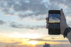 Bemannen Sie das Machen von Fotos des Sonnenuntergangs mit Smartphonekamera am bunten Abend des Sommers Stockbild