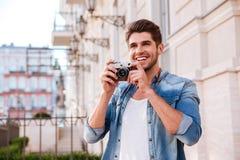 Bemannen Sie das Machen von Fotos mit alter Weinlesekamera auf der Straße Lizenzfreie Stockfotografie