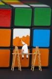 Bemannen Sie das Malen der Quadrate auf einem rubiks Würfel Stockbild