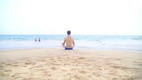 Bemannen Sie das Meditieren auf sandigem Strand in den Tropen stock footage