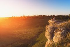 Bemannen Sie das Meditieren bei dem Sonnenuntergang, der auf Felsen am Gebirgshintergrund sitzt lizenzfreie stockfotos
