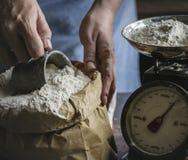 Bemannen Sie das Messen des Mehls durch die Gewichtungsskala stockfotos