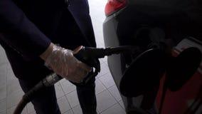 Bemannen Sie das Nehmen der heraus Kraftstoffdüse vom Auto und vollen Behälter des Qualitätsbenzins wieder tanken stock footage