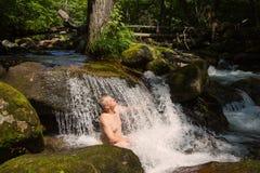 Bemannen Sie das Nehmen einer Dusche unter einem Wasserfall in einem Fluss Stockbild