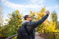 Bemannen Sie das Nehmen eines selfie in der Natur und das Lächeln Stockbilder