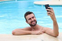 Bemannen Sie das Nehmen eines selfie an Erholungsorte Poolside auf Sommerferien Stockfotos