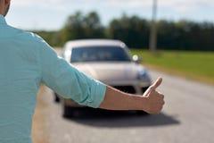 Bemannen Sie das Per Anhalter fahren und das Stoppen des Autos mit den Daumen oben Stockbild