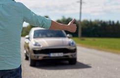 Bemannen Sie das Per Anhalter fahren und das Stoppen des Autos mit den Daumen oben Stockfoto