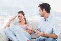 Bemannen Sie das Plädieren mit seinem Umkippenpartner auf der Couch Stockfotos