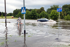 Bemannen Sie das Radfahren und Auto, die versuchen, gegen Flut auf der Straße zu fahren