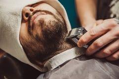 Bemannen Sie das Rasieren seines Bartes im Berufsfriseur Lizenzfreies Stockfoto