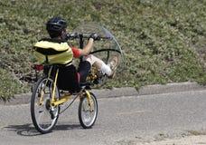 Bemannen Sie das Reiten eines eindeutigen Fahrrades mit einer Frontscheibe stockfotos
