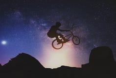 Bemannen Sie das Reiten eines Fahrrades, das einen Trick gegen auf Berg mit Milchstraße durchführt stockfotos