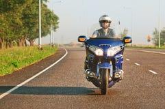 Bemannen Sie das Reiten eines Motorrades auf eine offene Straße Stockfoto