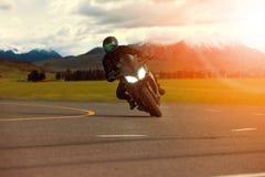 Bemannen Sie das Reitsportmotorrad, das in der scharfen Kurve mit travelin sich lehnt lizenzfreies stockfoto