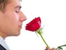 Bemannen Sie das Riechen einer Rose Lizenzfreie Stockbilder