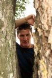 Bemannen Sie das Schauen durch Baum Lizenzfreie Stockfotografie