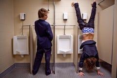 Bemannen Sie das Schauen zu einem einem anderen Mann in einer Toilette, die werid Sachen tut Stockfotos