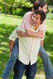 Bemannen Sie das Schauen zu seiner Seite beim seinen Freund auf seinem zurück tragen Stockbilder