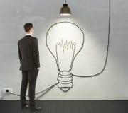 Bemannen Sie das Schauen zum Glühlampekonzept auf der Wand Stockbilder