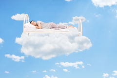 Bemannen Sie das Schlafen auf einem Bett in den Wolken Stockfotografie