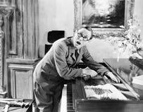 Bemannen Sie das Schreien mit seiner Hand, die in einem Klavier gefangen wird (alle dargestellten Personen sind nicht längeres le Stockbild