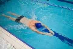 bemannen Sie das Schwimmen des vorderen Schleichens in einem Pool lizenzfreie stockfotos