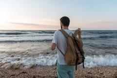 Bemannen Sie das Setzen auf einen Rucksack auf dem Hintergrund des Meeres Stockfotos