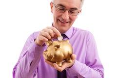 Bemannen Sie das Setzen der Münze in Sparschwein Lizenzfreie Stockfotografie