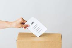 Bemannen Sie das Setzen seiner Abstimmung in Wahlurne auf Wahl Stockfotos