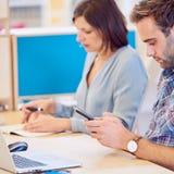 Bemannen Sie das Simsen an seinem Telefon mit Frau im Hintergrund Lizenzfreies Stockbild