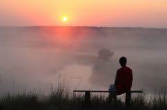 Bemannen Sie das Sitzen auf Bank und aufpassendem nebelhaftem Sonnenaufgang Stockbilder