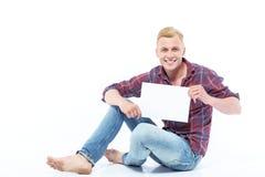 Bemannen Sie das Sitzen auf Boden mit Blatt Papier Stockfotografie