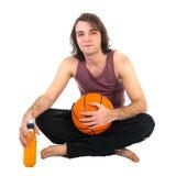 Bemannen Sie das Sitzen auf Boden mit dem Basketball und Orangensaft, lokalisiert am Weiß Stockbild
