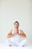 Bemannen Sie das Sitzen auf dem Bett, das Yoga mit Exemplarplatz tut Stockbild